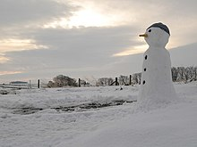Photograph of a snowman in a wintry landscape