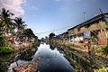 Slum area along a canal in Jakarta (6788717528).jpg