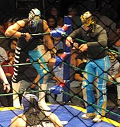 Picture of two masked men standing on the outside of the apron of the ring watching the match.