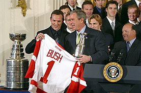 "A group of young to older men stand around an older man holding a red and white ice hockey jersey bearing the word ""BUSH"" and the number ""1"""