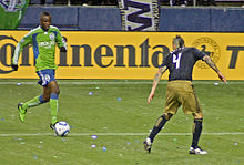 Zakuani dribbles towards an opposing player during a match