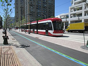 Harbourfront (Toronto) - In June 2015, a streetcar runs along Queens Quay between parkland (with a bicycle path) and the street (right)