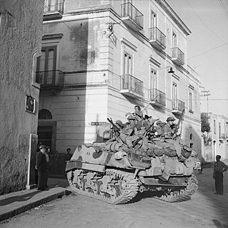 Lashmer Whistler - Sherman tank of the Royal Scots Greys carrying men of the 1/6th Battalion, Queen's Royal Regiment during mopping up operations in Torre Annunciata, Italy, 1 October 1943.