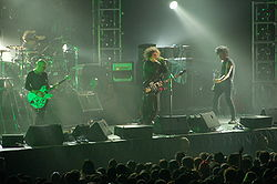 The Cure performing in August 2007. From left to right: Pearl Thompson, Jason Cooper, Robert Smith, and Simon Gallup