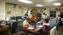 Several young men and women sit in office chairs working at computers around a room where the walls are covered in printed pages. A central wood table and bookcases are featured.