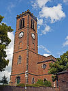 A two-storey brick church with a tall slim tower. It has clock faces and a battlemented parapet