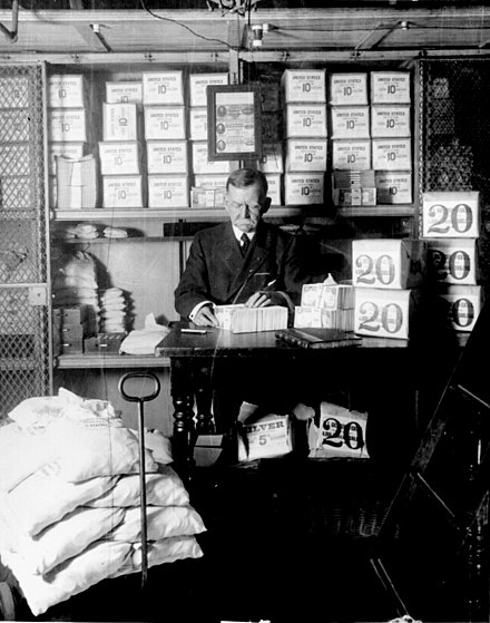 Treasury Department official, surrounded by packages of newly minted currency, counting and wrapping dollar bills. Washington, D.C., 1907. Treasury department official 1907.jpg