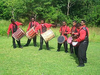 Tassa - The tassa band Trinidad and Tobago Sweet Tassa, founded and directed by Lenny Kumar (center). The photo includes three bass players (left), three tassa players (center), and one jhal player (right).