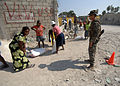 U.S. Marine Corps Lance Cpl. Matthew Gearheart, with Battalion Landing Team 3-2, Weapons Company, jokes with women carrying bags at a food distribution site in Carrefour, Haiti 100216-N-HX866-014.jpg