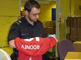 UK Border Agency - A UK Border Agency officer examines counterfeit football shirts upon their arrival in the United Kingdom