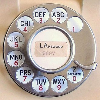 Telephone number - Face of a 1939 rotary dial showing a 2L-4N style alphanumeric telephone number LAkewood-2697.