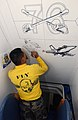 US Navy 031017-N-4616B-104 Aviation Boatswain Mate Airman Eliseo Granado, from San Antonio, Texas, draws a mural on the stairway leading to the Commanding Officer's passageway aboard USS Ronald Reagan (CVN 76).jpg