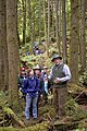 US Navy 050618-N-3390M-194 Walter Briggs, assigned to Naval Facilities Engineering Command, Poulsbo, Wash., right, leads a guided tour of the Jim Creek Old Growth Forest.jpg
