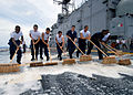 US Navy 070706-N-5588M-003 Aboard amphibious assault ship USS Nassau (LHA 4), Sailors from the crash and salvage team sweep down the flight deck during an aqueous film forming foam (AFFF) countermeasure wash down.jpg