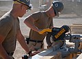 US Navy 071101-N-3857R-002 Builder Constructionman Recruit Adam Moenkedick, assigned to Naval Mobile Construction Battalion (NMCB) 1, cuts a piece of wood to be used in construction of a crow's nest watch station.jpg
