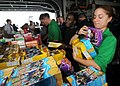 US Navy 080726-N-9898L-009 Aviation Machinist's Mate Airman Ashley Schumm picks up boxes of cookies from Girl Scouts participating in Operation Cookie Drop.jpg