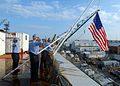 US Navy 080811-N-3885H-029 Quartermaster 1st Class Christopher Dorner, left, Airman Ryan Miller and Aviation Boatswain's Mate (Handling) Airman Ryan Jones hoist the American flag over the fantail of the aircraft carrier Pre-Com.jpg