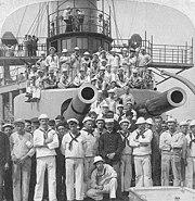 crewmen pose under gun turrets of the USS Iowa