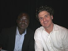 A young black man in glasses and a suit (Valentino Achak Deng) sits to the right of a Caucasian man with wavy black hair wearing a white shirt (Dave Eggers)
