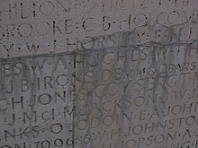Names carved into a wall are covered in unidentified mineral deposits. Many of the names are no longer readable or are heavily distorted.