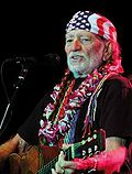 An elderly man holds a guitar while in front of a microphone. He has white facial hair and wears a United States flag bandana.