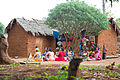 Women seated outside a hut.jpg