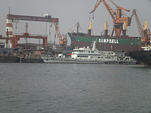 patrol boat berthed among tankers in a shipyard, gantry cranes in the background