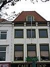 foto van Huis met gepleisterde lijstgevel. Fries voorzien van consoles en panelen. Schilddak, twee houten pirons en dakkapel met vleugels. Pui modern