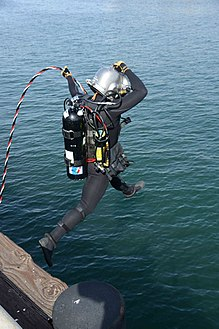 A surface supplied diver entering the water with a diver's umbilical laid up from differently coloured twisted hoses and cables leading back to the boat