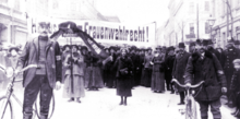 Photograph of a group of women surrounded by policemen during a women's suffrage demonstration in Vienna