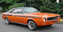 Shows a 1969 AMC Javelin featuring optional in Big Bad Orange paint and optional black vinyl covered roof and full length body side stripes