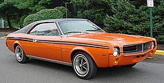 Shows a 1969 AMC Javelin featuring optional in Big Bad Orange paint and optional black vinyl covered roof and full-length bodyside stripes