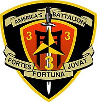 "A black shield with a red interior and a gold border. On the top is written ""America's Battalion"" and on the bottom written ""Fortes Fortuna Juvat."" The red interior has three ""3""'s in the center with a sword running through it with a caltrop."