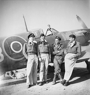 No. 451 Squadron RAAF -  May 1944, Poretta, Corsica. In front of a Spitfire undergoing servicing are pilots (left to right) F/O W. W. Thomas of Malvern, SA; F/O E. C. House DFM DFC of Gnowangerup, WA; S/Ldr E. E. Kirkham of Concord, NSW, and; F/O H. J. Bray of Moolcolah, Qld, not long after claiming four FW190s over Italy.