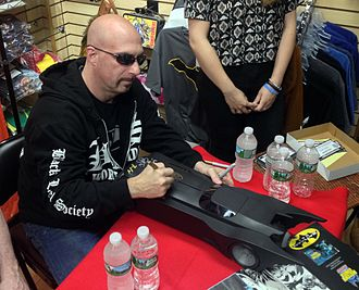 Greg Capullo - Capullo signing a Batmobile toy during an appearance at Midtown Comics