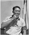 A Japanese man smoking a cigar during Relocation - NARA - 195541.tif