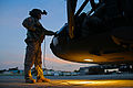 A U.S. Army UH-60 Black Hawk helicopter crew member assigned to the Puerto Rico Army National Guard inspects the aircraft prior to conducting night flight training at the aviation support facility in Isla 140902-Z-KD550-656.jpg