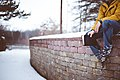 A person sitting on a wall in the snow (Unsplash).jpg