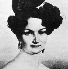 A young woman with black hair pinned up looking sternly