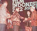 Ali Moertopo shaking hand of Adam Malik, Festival Film Indonesia (1982), 1983, p66.jpg