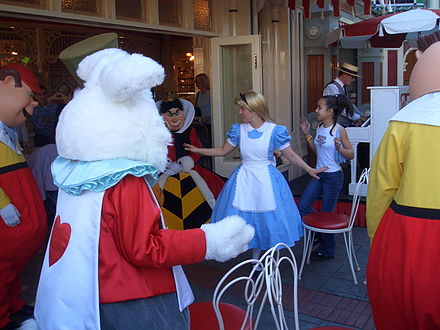 "Alice and characters from her movie host ""Disneyland Musical Chairs"" at Coca-Cola Refreshment Corner, accompanied by a ragtime pianist Alice plays musical chairs.jpg"