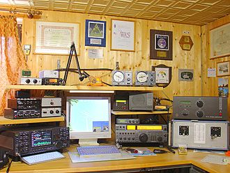 Amateur radio - An example of an amateur radio station with four transceivers, amplifiers, and a computer for logging and for digital modes. On the wall are examples of various amateur radio awards, certificates, and a reception report card (QSL card) from a foreign amateur station.