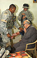 BAGHDAD, IRAQ -- Sgt. Clydell White, of Houston, TX, a medic with the 1-10 Mountain Division's 2nd Battalion, 22nd Infantry Regiment, checks the blood pressure of an elderly Iraqi citizen while DVIDS12522.jpg