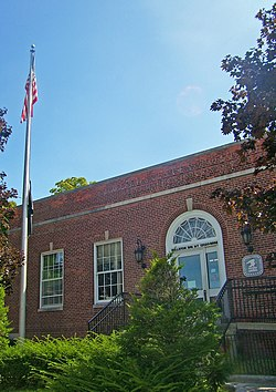 View of some of the front of the post office with a flagpole in front and some lens flare in the blue sky