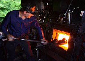 Fireman (steam engine) - A fireman working on a German Class 52 steam locomotive.
