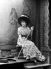 Full length monochrome photograph of a woman seated on a low stool in front of a painting and facing slightly to her right. She wears a high-waisted flowered dress with a solid colour sash and a broad-brimmed hat decorated with flowers and holds a long walking stick.