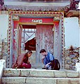 Buddhist monk and American tourist playing checkers in front of a monastery gate, China, October 1999.jpg
