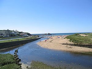 Bude - View of the beach in Bude and the canal coming to an end as it reaches the sea lock (on left of image)