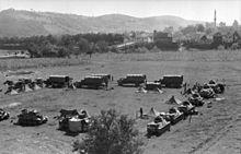 uma fotografia em preto e branco de veículos blindados alemães e tendas em uma formação quadrada em campo aberto