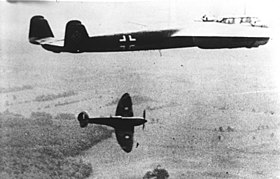Twin-engined, twin-finned aircraft in flight with single-engined aircraft in lower background